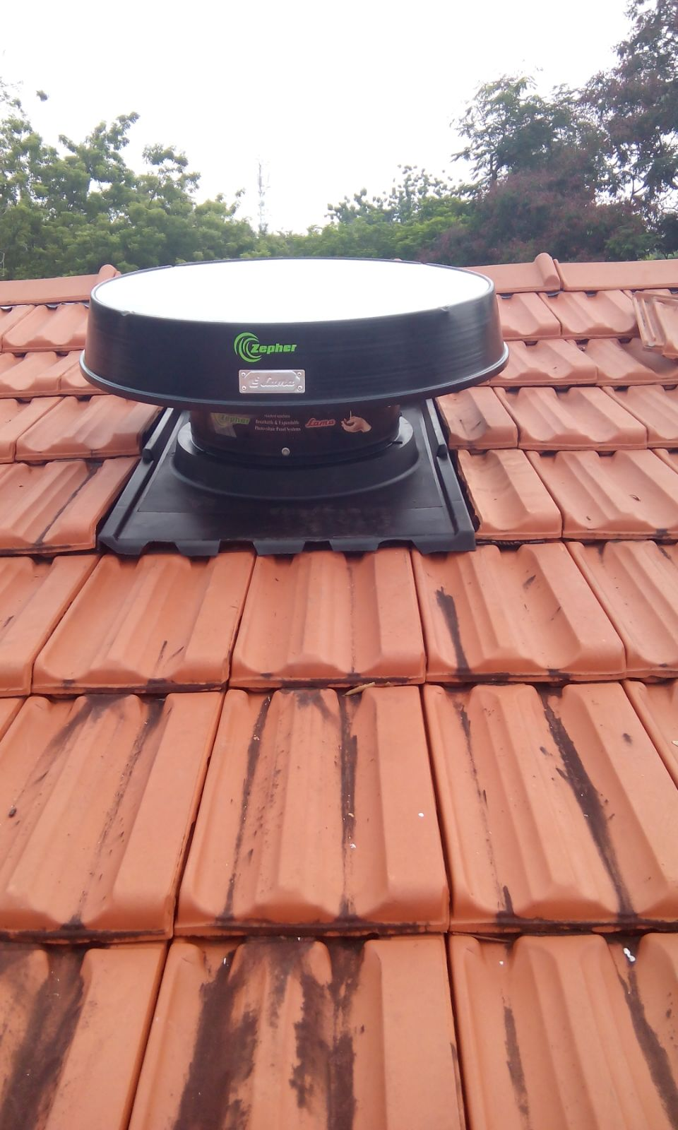 Solar roof ventilator on tile roof